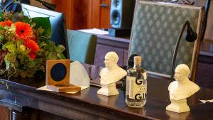 Prismedalj, blommor och Runebergsstatyer samt en flaska gin.