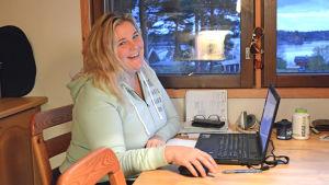 en kvinna som sitter vid matbordet med en bärbar dator framför sig.