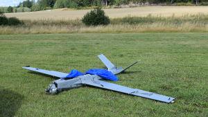 En drönare på gräset. Drönaren är av modellen som ser ut som ett litet flygplan. Den har skadats vid landningen.