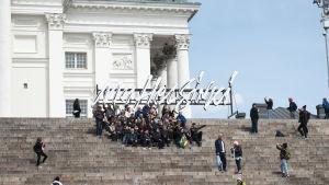 Turistit ottavat yhteiskuvaa Helsingin tuomiokirkon portailla.