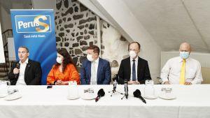 Män och kvinnor sitter bakom ett bord. Alla bär munskydd utom en man längst till vänster. Sannfinländska politiker i Åbo 26.8.2020.