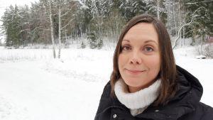 Saija Westerlund-Cook, en dam med rakt mörkt hår, står i ett snöigt åker- och skogslandskap.