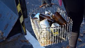 En hand håller i en potatiskorg i metall. Korgen är fylld med leriga flaskor och annat skräp.