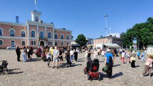 Människor står i solskenet på Lovisa torg.