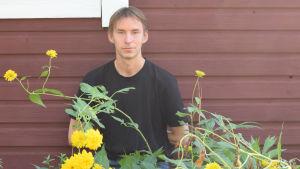 En man står vid en rödmyllad stuga, framför har han gula höga bommor. Sommar.