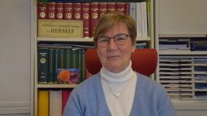 En kvinna med kort hår, glasögon och ljusblå jumper sitter bakom ett skrivbord. Bakom en bokhylla med lagböcker och mappar.