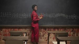 En rödklädd kvinna ritar vita streckgubbar på svarta tavlan i ett klassrum.
