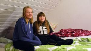 Två systrar som sitter på sängen i deras rum