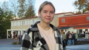 Portättbild på Erin Nylund, en tonåring med långt blont hår i hästsvans och svart-vit rutig jacka. I bakgrunden en skola och skolgård med elever. Höst, klart väder