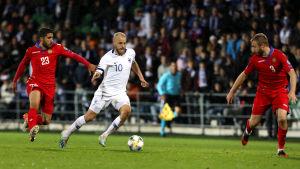 Teemu Pukki dribblar mellan två rödklädda fotbollsspelare.