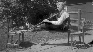 """En man leker leken """"sko tuppen"""", där han balanserar sittande på en stång. Bilden är tagen 1931 i Ingå."""