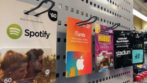 Presentkort på tjänster av Spotify, iTunes, Habbo, Stadium samt H&M hänger på en ställning i en butik.