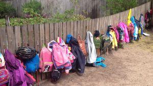 Skolväskor och jackor hänger på ett staket på eftisgård.