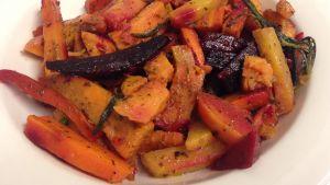 Ugnsbakade rotfrukter, bla morot, batat och rödbeta skurna  i stavar på en vit tallrik.