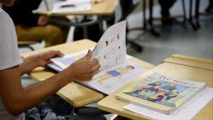 En elev bläddrar i en finsk lärobok i skolan.