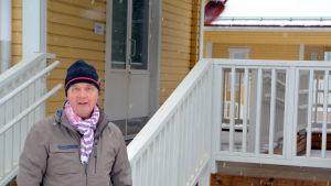 Man står utanför daghemsbyggnad i lätt snöfall.
