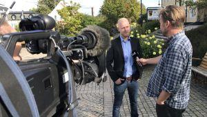 Svt-journalist intervjuar André af Geijerstam framför tv-kamera intill Sjöbo kommunhus.