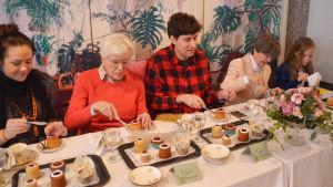 Fem personer sitter på rad bakom ett bord och äter Runebergstårtor.