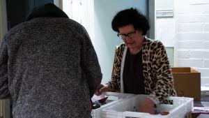 Ritva Koljonen tittar ner i matlådan för att ge mat åt en annan person.