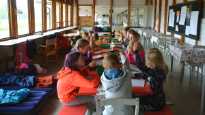 Barnen sitter inomhus kring ett bord med mappar och papper framför sig.