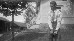 En man lyfter ett järnspett vågrätt. Bilden är tagen 1930 i Bromarf.