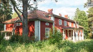 Varjakansaaren vanhan sahakylän päärakennus, punavalkoinen kaksikerroksinen puutalo, edessä kuisti.