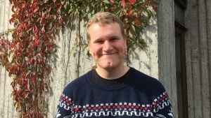 Kristofer Dahlgren framför grå vägg med röda blommor.
