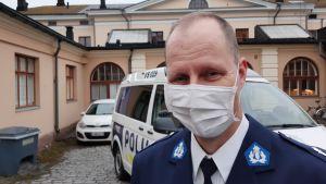 Fred Lindblom, en man med tunt ljust hår, vitt munskydd och polisuniform, står framför en polisbil.