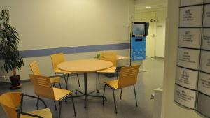 Ett tomt bord med stolar runt i en korridor.