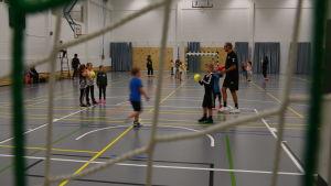 Barn spelar handboll inne i en idrottssal.Kastar en gul boll till varandra.