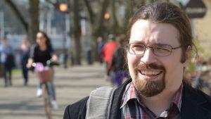 Petter Skult, en man med glasögon, mustasch och skägg, står på en gågata.