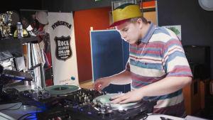 Nuori mies dj:nä miksauspöydän ääressä liikuttaa levylautasta toisella kädellä