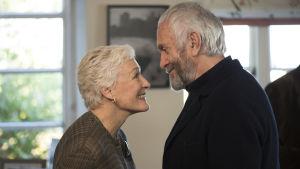 Joan (Glenn Close) och Joe (Jonathan Pryce) ser på varandra och ler.