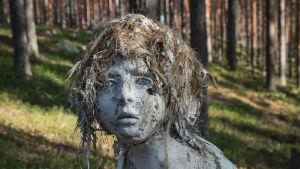 Lasta muistuttava istuva veistos metsässä, rapistunut, sammalta