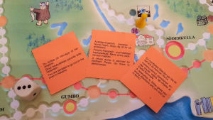 Närbild på chanskort ovanpå brädspelet Sibbo-vargen.
