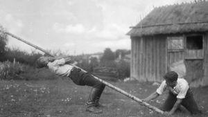 En man klättrar uppför en sluttande stång utan att använda benen som hjälp. Bilden är tagen 1930 i Sund, Åland.