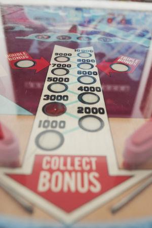 """Lähikuva flipperpelistä: nuolia, numeroita ja teksti """"triple bonus""""."""