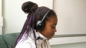 ung flicka med svart hår och brun hy och vit jacka. Fotad från sidan.Hon lyssnar på något i hörlurar
