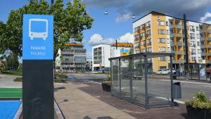 Till vänster syns en skylt som det står Nickby på, till höger syns en busshållplats invid Stora Byvägen. Det är en del av Nickby bussterminal som syns.