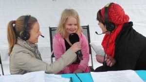 Flicka blir intervjuad av Yles reportrar.