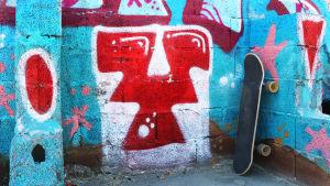En rullbräda står lutad mot en vägg som är täckt av graffiti.