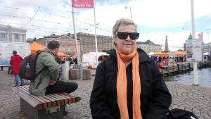 En kvinna i mörka solglasögon sitter vid kajen på Salutorget i Helsingfors.