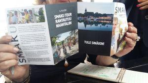En dam håller i en broschyr för matfestivalen Smaku tour i Nådendal.
