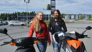 Två flickor som står bredvid sina mopeder