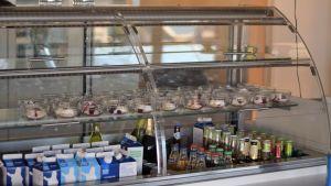 Ett fyllt vitrinskåp med drycker och portionsskålar med efterrätter.