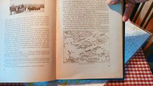 Henrik sundbäck visar en bok med en karta över hur trupperna stod.