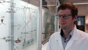 Axel Meierjohann, klädd i en vit labbrock i ett laboratorium.