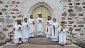 Lucia med sex tärnor ute på kyrktrappa. De är klädda i vita kappor av fuskpäls.