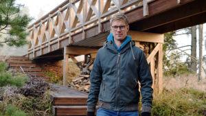 Jonas Lundberg går vid en gångbro i trä.