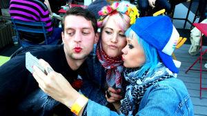 Bild på en kille och två tjejer som tar en selfie.